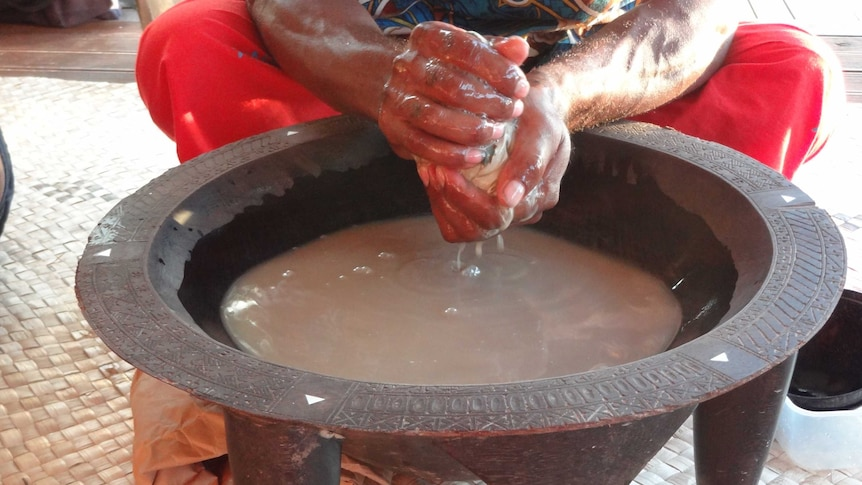 A man squats behind a large carved bowl with feet while making the traditional brown brew with his hands