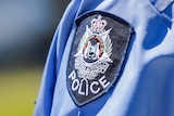 A WA Police badge on an officer's shirt shoulder.