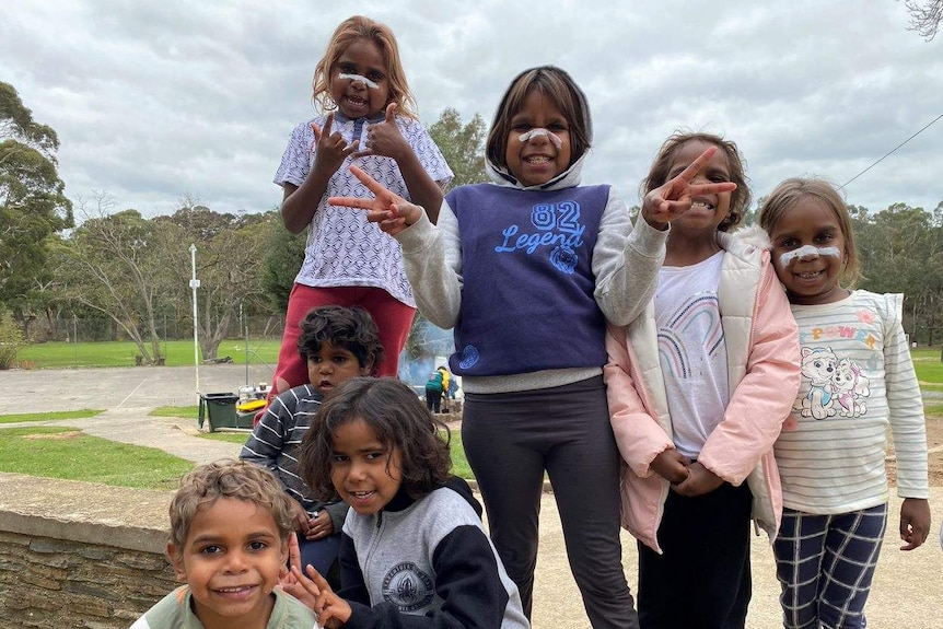 A group of Aboriginal children with white paint on their noses in front of a lawn