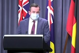 A suited man wearing a blue surgical mask looks up from a lectern.