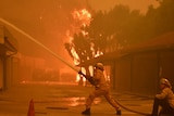 Firefighters hose down a condo unit during the Woolsey Fire in Malibu.