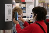A woman in a red jacket and a face mask scans a QR code at a supermarket.