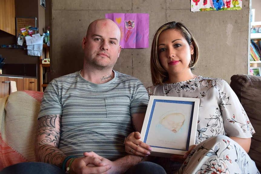 A man and woman sit next to each other, looking straight ahead. The woman holds a portrait of their stillborn son.
