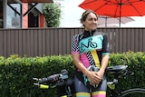 A woman wearing a Cycling Mums Australia jersey leans against her bike in front of a hedge.