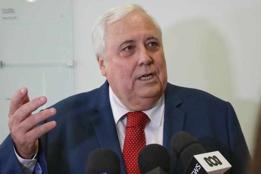 Clive Palmer, wearing a red tie, gestures while speaking into microphones in a hallway.