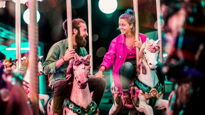 Man and woman ride carousel together holding hands for a story about not feeling like sex in a long-term relationship.