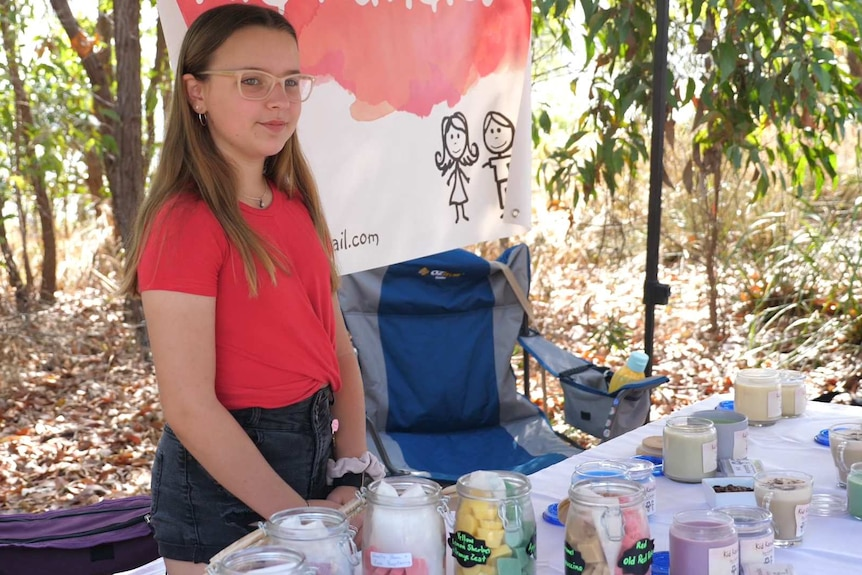 girl with glasses and red top stands selling candles in an area surrounded by trees.