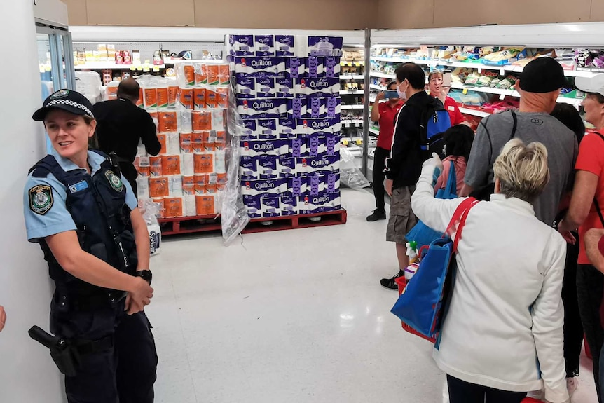 Two police officers watch a line of customers in a shop waiting to buy toilet paper