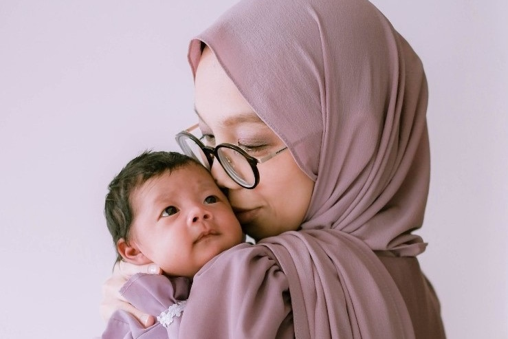 A photo of Indiana, who wears a beige hijab, holding her baby daughter.