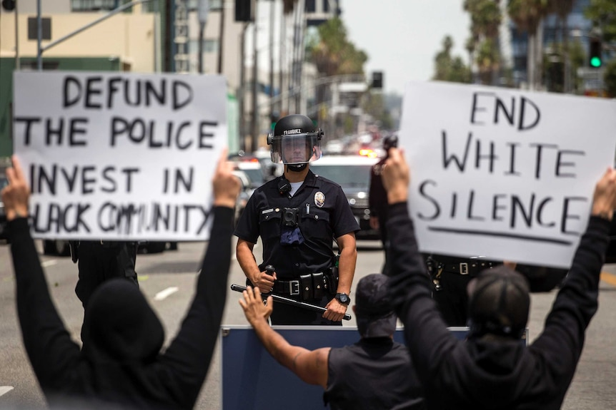 Demonstrators holding signs confront a police officer, Tuesday, June 2, 2020, in the Hollywood section of Los Angele
