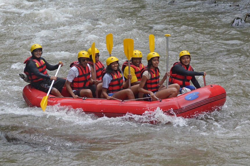 The Obama family are seen smiling as they sit in a raft in rapid waters in Bali.
