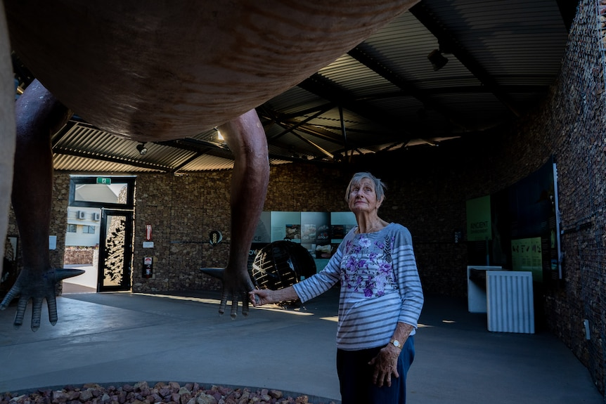 An elderly woman stands underneath the belly of a lifesize dinosaur statue and holds its hand.