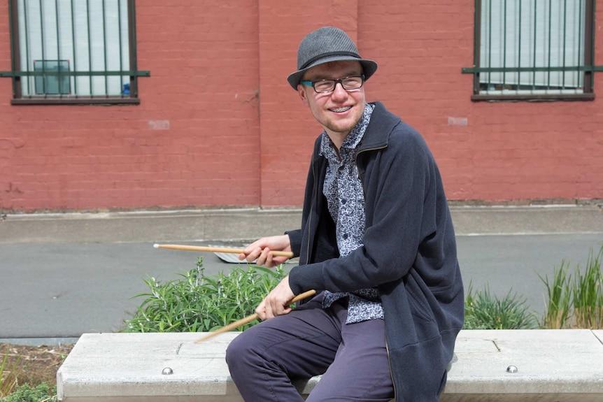 Jerrah Patston plays with his drum sticks on a park bench