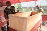 Two men standing on either side of a plywood coffin, with other coffins wrapped in plastic behind them.