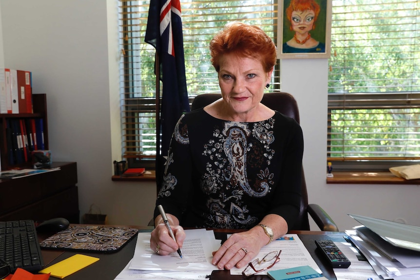 Middle aged woman sitting at desk with pen poised over papers.