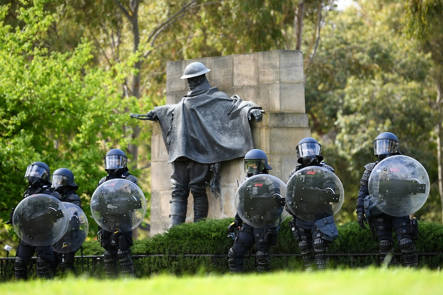 Riot police with shields and helmets stand in a line at the Shrine in front of a brass sculpture of a soldier.