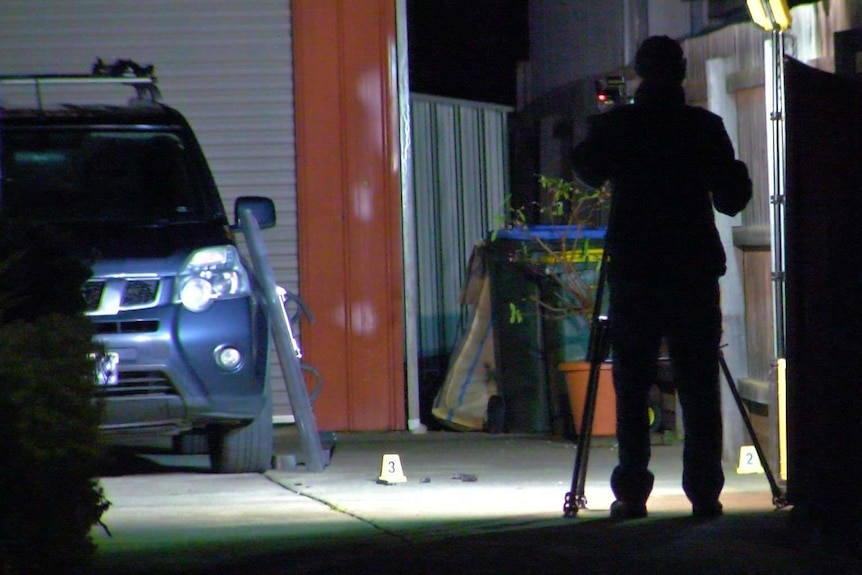 An area lit by a spotlight near a car in a driveway with a police officer taking photos.