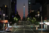 A long lens shot of a deserted streetscape with a lit up monument in the background