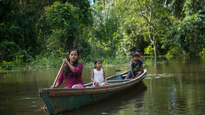 A woman paddles a canoe with two children behind her.