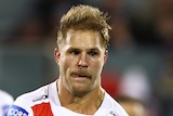 St George Illawarra Dragons player Jack de Belin passes a football. Teammate Andrew McCullough is blurred behind him.