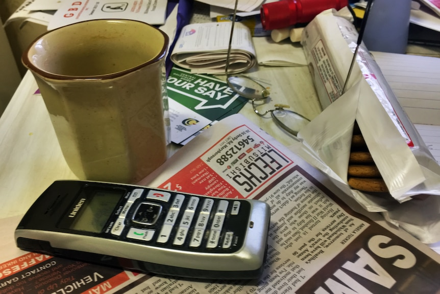 Cordless phone on messy kitchen table