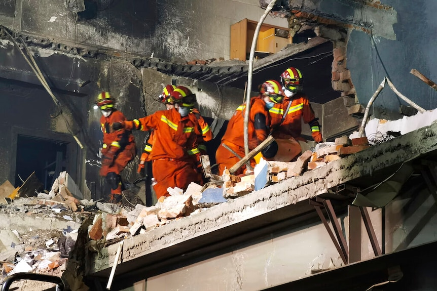 People in orange jumpsuits and helmets carry what appears to be a stretcher through a burnt-out building.