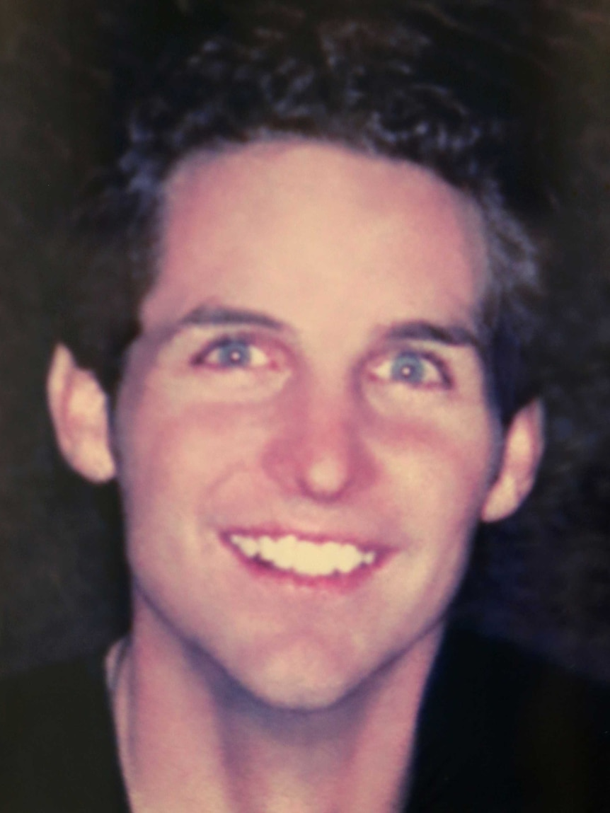 A photo of a blue-eyed young man with dark hair smiling at the camera.