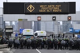 A large group of riot police in black hold up shields walking under a sign that says 'west gate fwy protestors seek alt route'