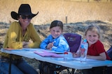 A mother sits at a camp table helping her two girls do school work