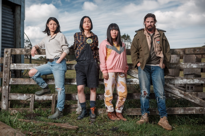 Three Asian women and a white man stand in a row/lean on a farm fence