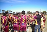 A group of players stand around while assistant coach Brenton Meynell goes through the game plan.