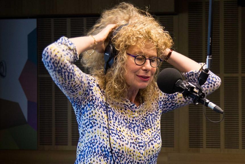 Kohn in studio in front of mic holding up hands to put headphones on.