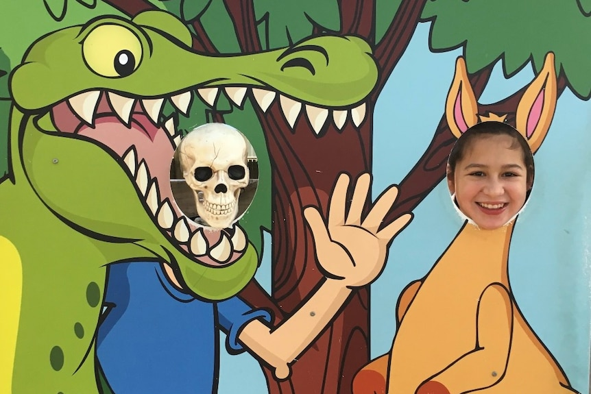A skeleton and a young girl put their heads into holes, pretending to be a crocodile and kangaroo.