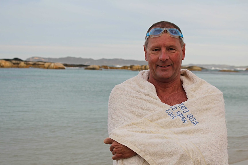 A man wrapped in a white towel with goggles on his head stands on a beach