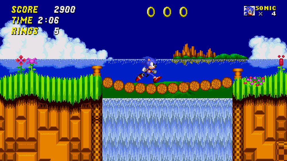 In a scene from a 2D video game a blue hedgehog-like character runs across bridge towards lush grass in location near the ocean.