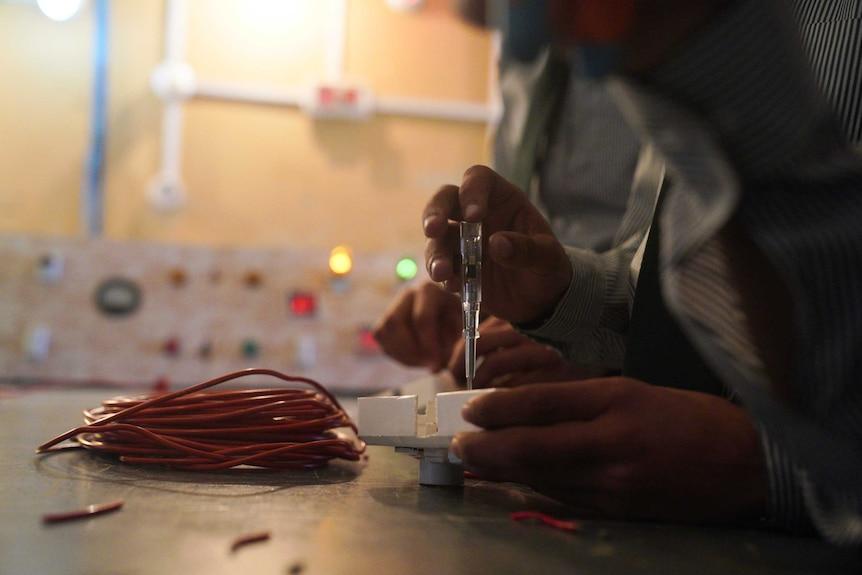 A boy fixes a light switch