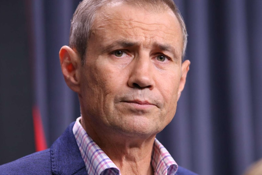 A close up of Roger Cook's face with a blue curtain background, looking concerned.