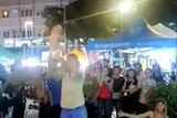 A Russian man holds a baby up in Malaysia street performance.