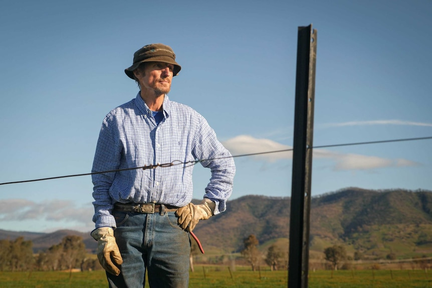 Tony Jarvis wears a hat, gloves, jeans and blue shirt, he's standing behind a fence he's rebuilding, with green paddocks behind.