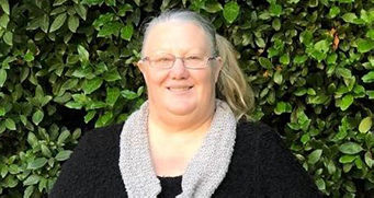 In front of a green hedge, a woman in glasses and black jumper, with light scarf, smiles.