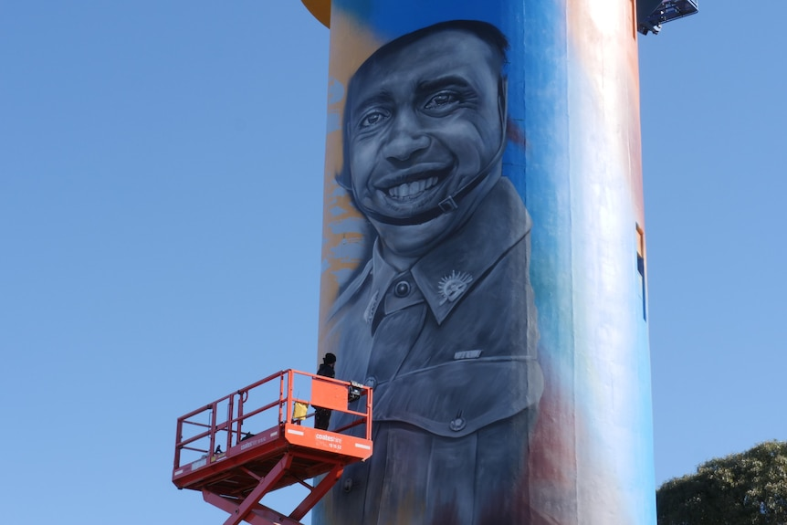 painted water tower with portrait of indigenous soldier smiling