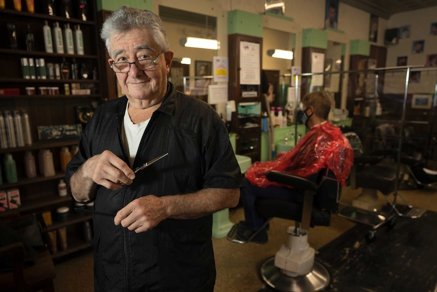 A man in glasses holding a pair of scissors in a barber shop