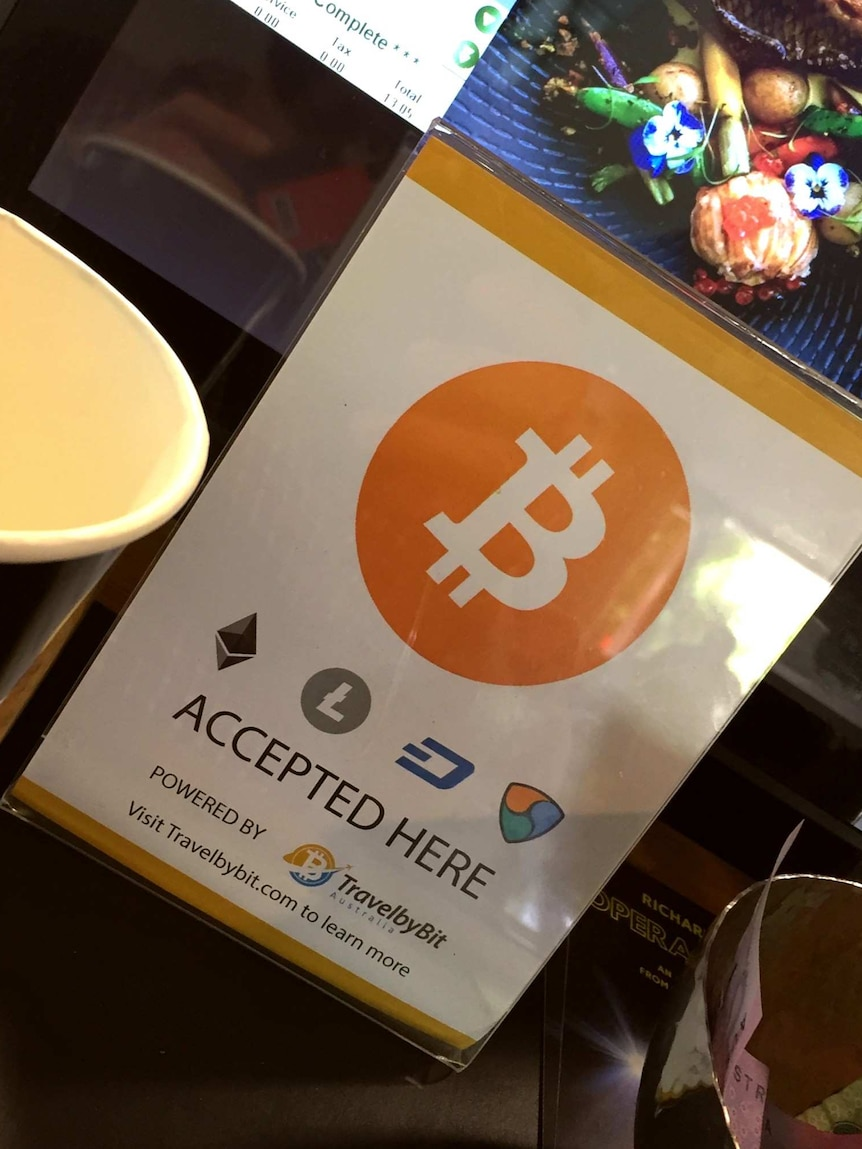 A sign advertising bitcoin is accepted is displayed in front of a cafe cash register.
