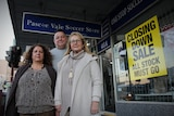 A man and two women stand in front of a Pascoe Vale Soccer Store sign. There is a yellow closing down sticker on the window