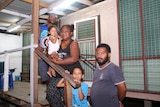 Woman, two children and two men face camera in front of house.