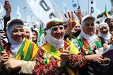Kurdish women shout slogans and flash victory signs in Istanbul during an election rally