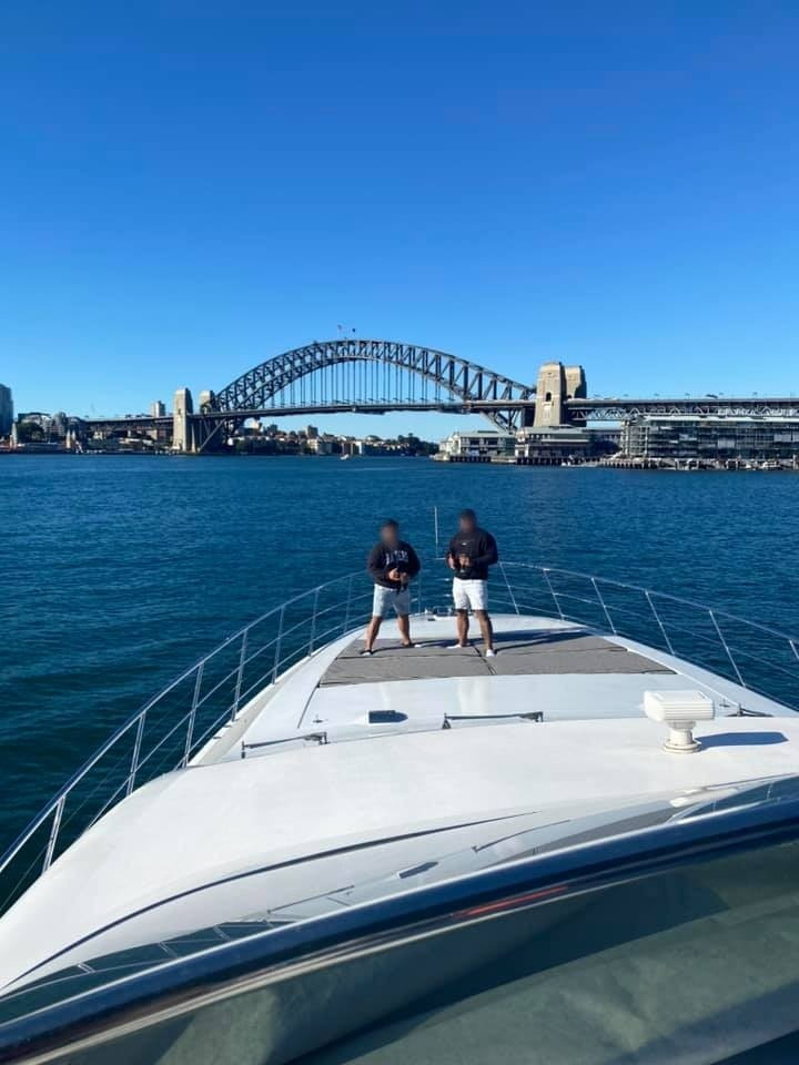 Two men stand on the bow of a large boat with Sydney Harbour Bridge in the background.