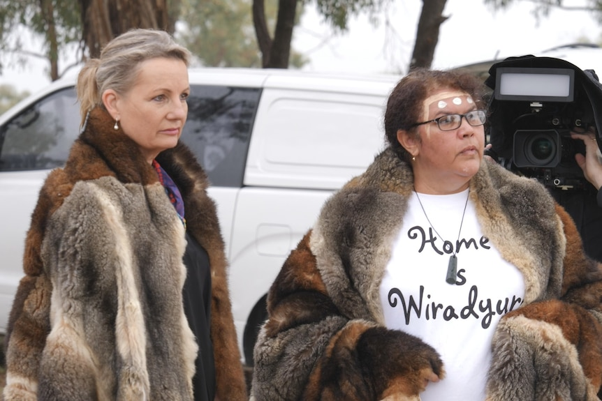 Two women wear possum skin cloaks in front of a white van and a man holding a TV camera.