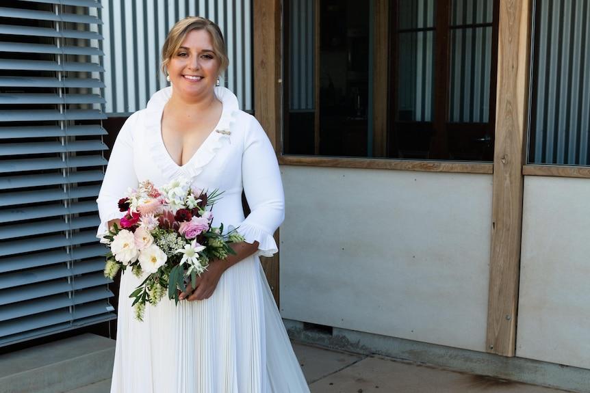 A smiling bride in a wool wedding dress