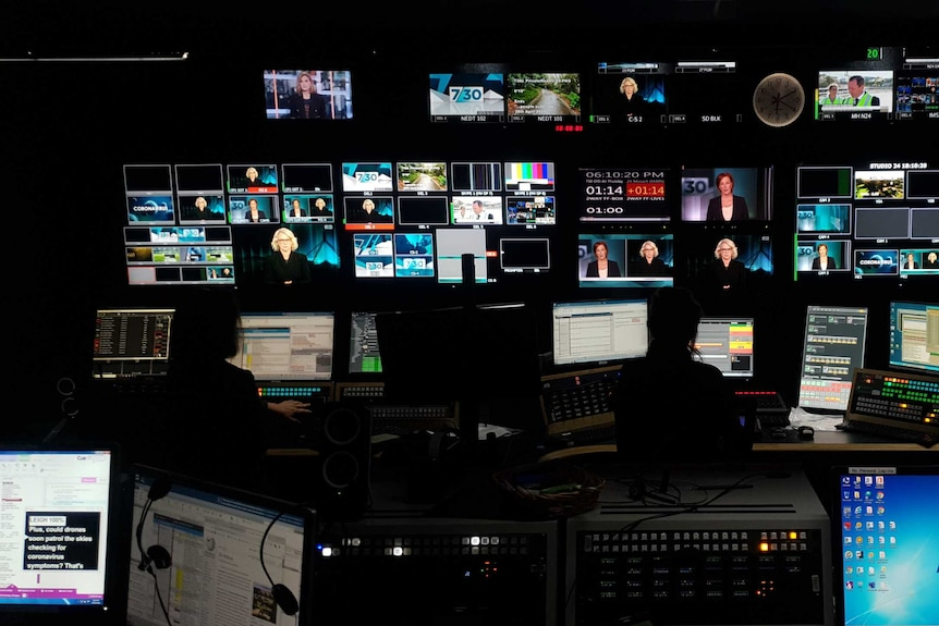 Wide shot inside studio control room with multiple TV monitors showing Leigh Sales and Laura Tingle on screen.